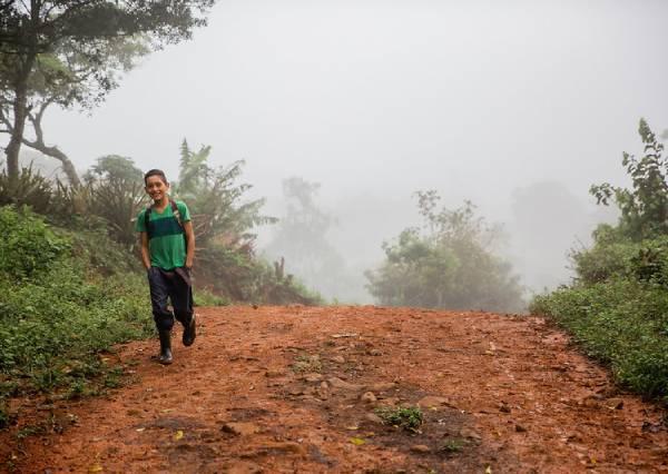 niño caminando en camino de tierra