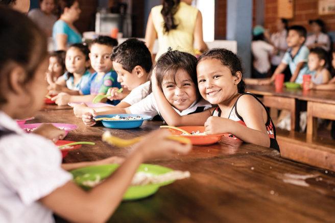 niños disfrutando almuerzo escolar en centro de fabretto