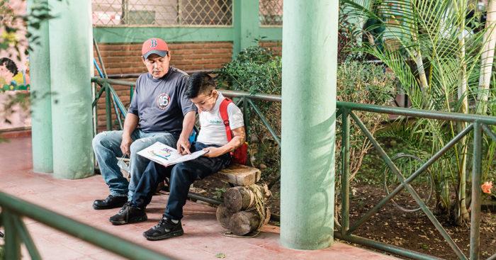 estudiante lee acompañado de su padre